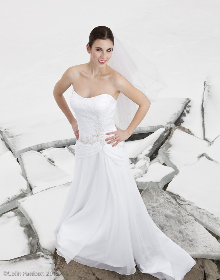 Bride posing in front of an icy lake