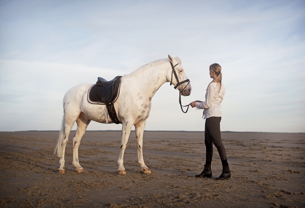 lifestyle image ponytailed woman with horse on beach