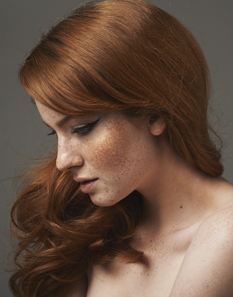 freckled redhead with curly hair and winged eyeliner